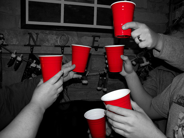 selectively colored red plastic cups held up by partygoers