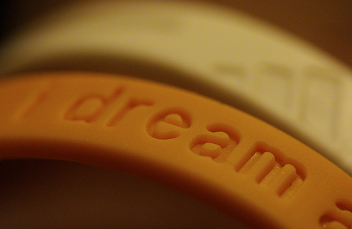 "orange rubber band bracelent that says ""dream"""