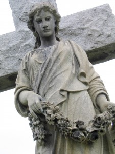 a stone angel with a garland of flowers in front of a cross