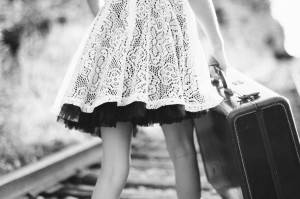 black and white photo of woman holding a suitcase