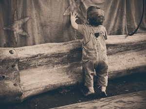 vintage photo of child playing with stars on a curtain